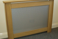 New England radiator cabinet in natural oak with a oriental design grille in silver