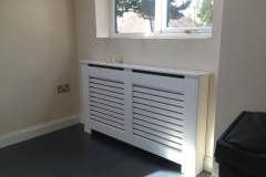 New England radiator cabinet design finished in satin white with a horizontal grille on the two grille openings