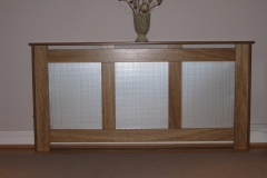 New England design radiator cover finished in natural oak with a oriental silver grille on the three openings
