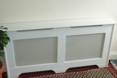 Old England design radiator cabinet finished in primer white with a Oregon white faced grille
