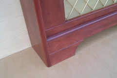 Studley design finished in mahogany stain and clear lacquer showing the lower decorative rail and a regency brass grille
