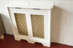 Studley radiator cabinet finished in satin white with a Regency brass grille