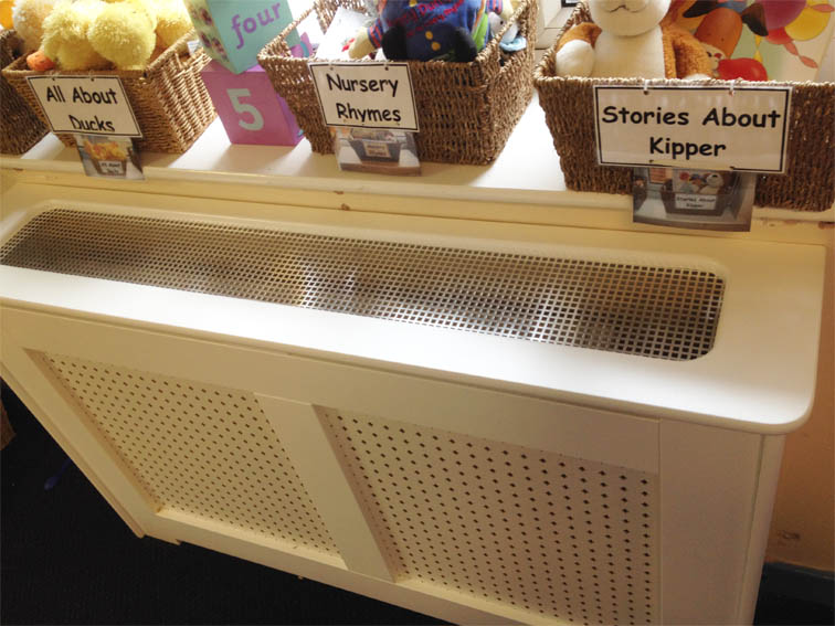 radiator cabinet on a storage heater with a vented top shelf which is removable